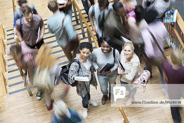 Porträt von drei Studenten an der Universität  andere Studenten gehen die Treppe hinunter