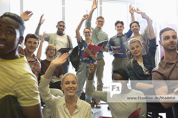 Lächelnde Universitätsstudenten heben ihre Hände beim Seminar