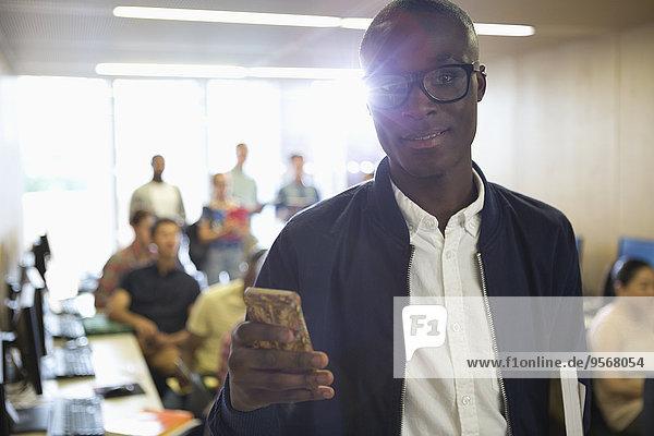 Portrait eines Studenten mit Smartphone im Klassenzimmer
