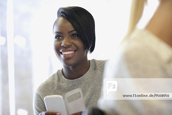 Lächelnder Student mit Smartphone im Seminar