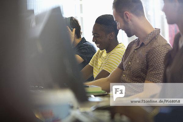 Universitätsstudenten beim Sprechen und Lernen am Computer im Klassenzimmer
