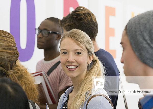 Porträt eines Studenten  der im Flur steht und im Hintergrund spricht