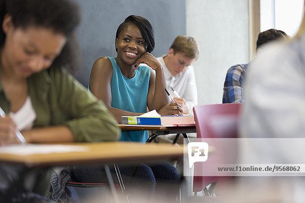 Lächelnder Student sitzt am Schreibtisch mit der Hand am Kinn