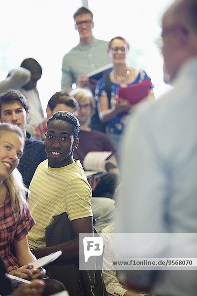 Fokussierte Studenten  die dem Professor beim Seminar im Klassenzimmer zuhören.