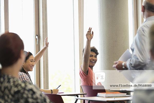 Lächelnde Universitätsstudenten heben die Hand beim Seminar