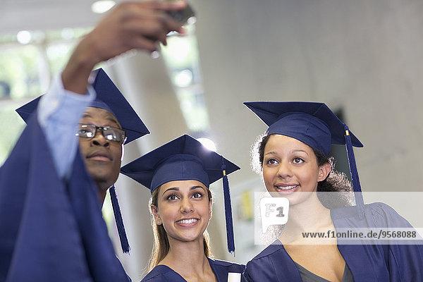 Drei Studenten  die sich nach der Abschlussfeier selbstständig machen