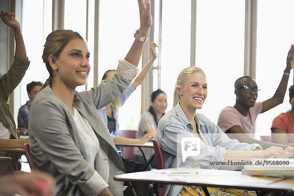 Universitätsstudenten heben während des Seminars die Hand