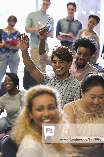 Studenten heben die Hand beim IT-Seminar