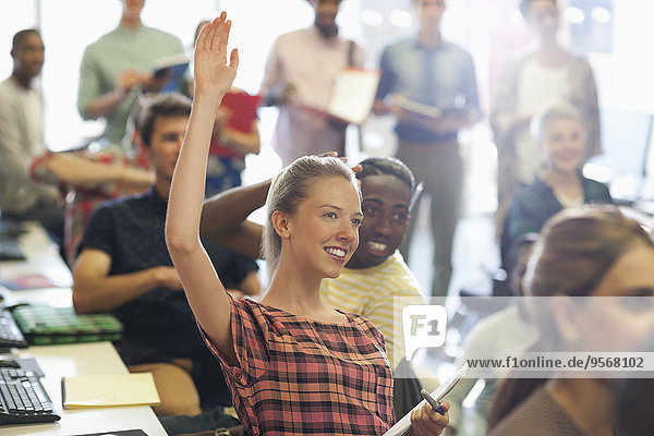 Hochschulstudent hebt Hand beim IT-Seminar