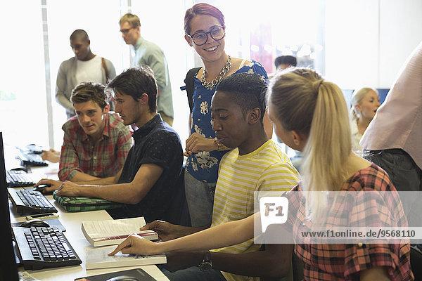 Universitätsstudenten  die am Computer studieren und diskutieren