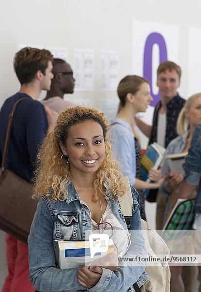 Eine Studentin hält Bücher und lächelt mit einer Gruppe von Studenten im Hintergrund.