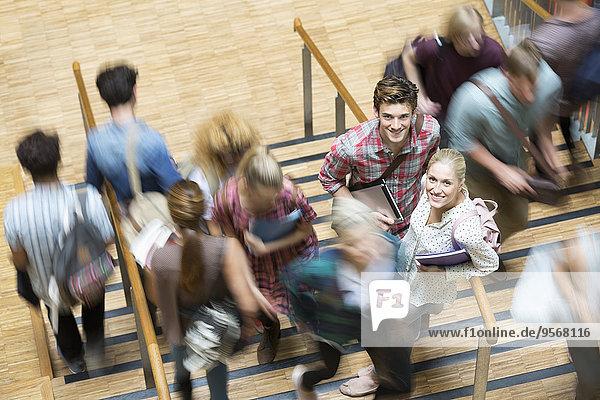 Schüler  die in den Pausen auf die Kamera schauen und auf der Treppe stehen