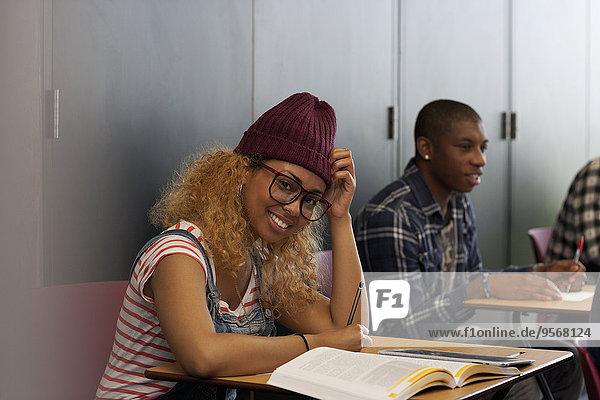 Studentin sitzt während der Vorlesung am Schreibtisch und lächelt vor der Kamera.