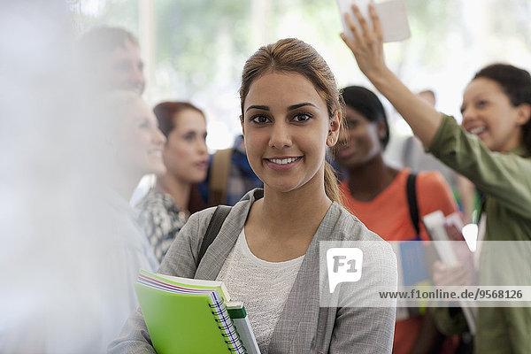 Lächelnde Studentin mit Büchern in der Pause