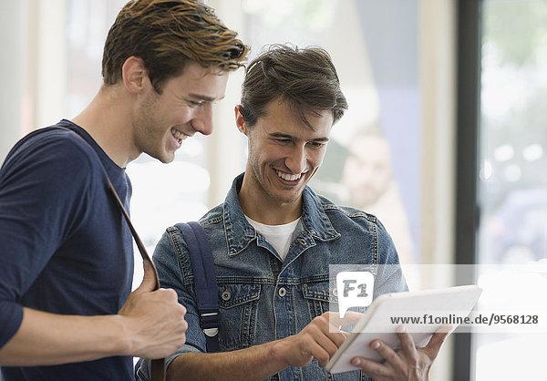 Zwei männliche Studenten beim Betrachten des digitalen Tabletts und beim Lachen