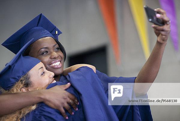Zwei lächelnde Studentinnen bei der Abschlussfeier