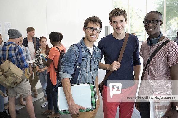 Drei lächelnde männliche Studenten  die zusammen mit anderen Studenten im Hintergrund stehen.