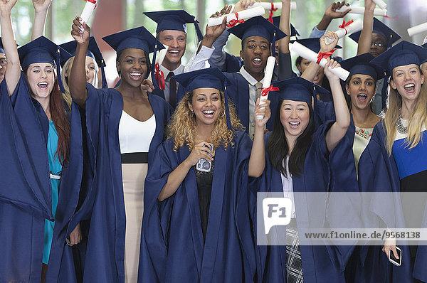 Gruppe von Studenten in Abschlusskleidung  die gemeinsam für ein Gruppenportrait posieren.