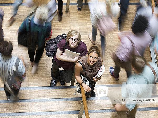 Schülerinnen und Schüler schauen in die Kamera und stehen während der Pause im Flur.
