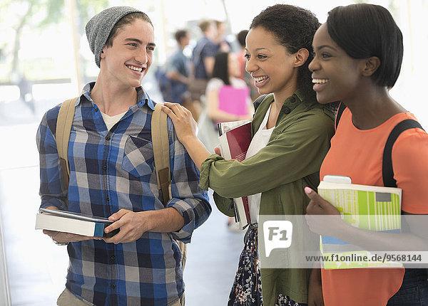 Studenten mit Büchern und Lachen mit anderen Studenten im Hintergrund