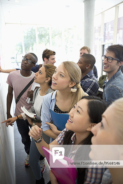 Erhöhte Ansicht der Gruppe von Schülern  die während der Pause auf das Schwarze Brett schauen.