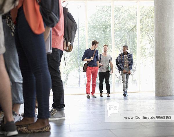 Drei männliche Studenten  die den Flur entlanggehen und mit einem großen Fenster im Hintergrund sprechen.