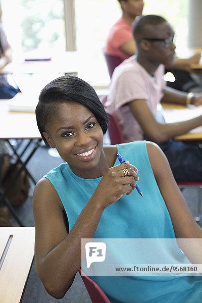 Eine Studentin lächelt während der Vorlesung mit anderen Studenten im Hintergrund.
