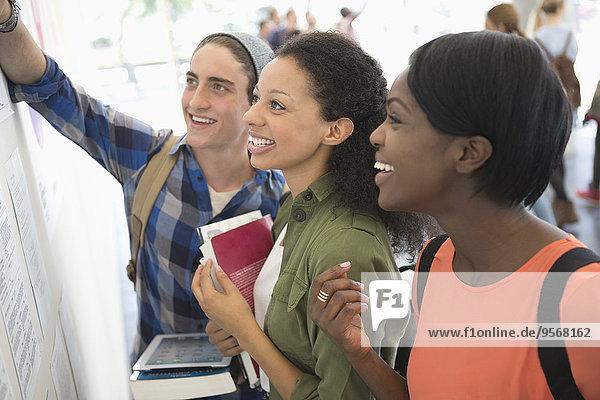 Drei lächelnde Schüler schauen auf Informationstafel  halten Bücher und digitales Tablett.