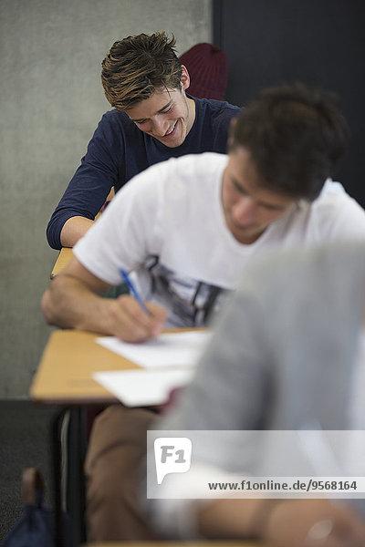 Blick auf lächelnde Schüler  die während einer Prüfung im Klassenzimmer am Schreibtisch sitzen