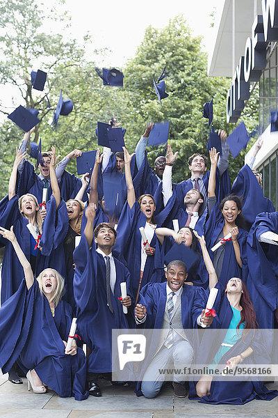 Gruppenporträt von Studenten in Promotionskleidern  die Mörtelbretter in die Luft werfen.