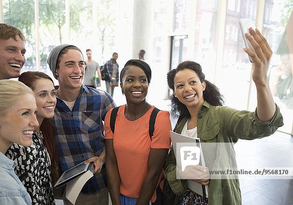 Gruppe von lächelnden Studenten mit Büchern und digitalem Tablett  die Selfie mit Smartphone nehmen