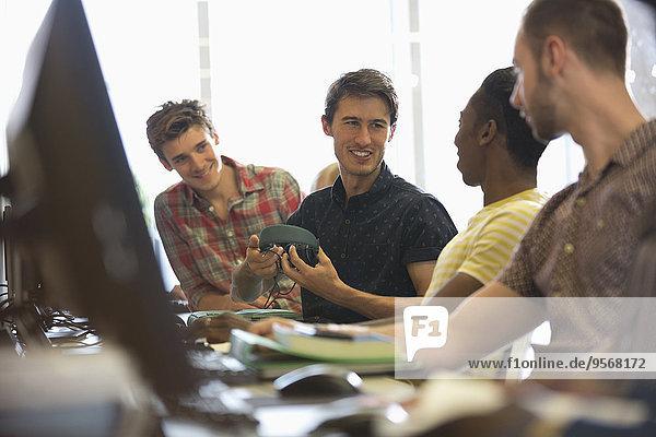 Gruppe von lächelnden männlichen Studenten  die an Schreibtischen mit Computern sitzen und reden.