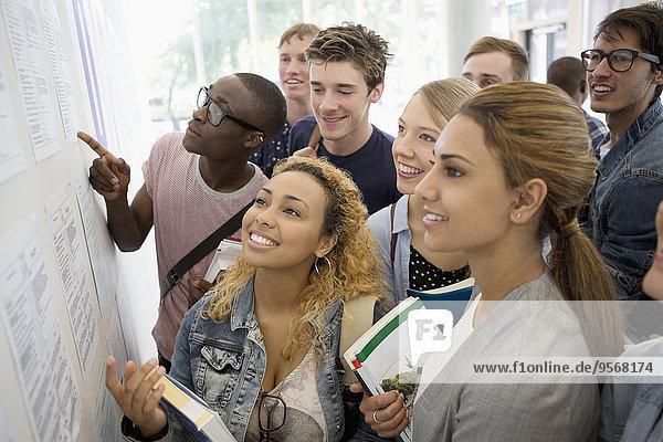 Gruppe von lächelnden Studenten mit Büchern und Blick auf Informationstafel