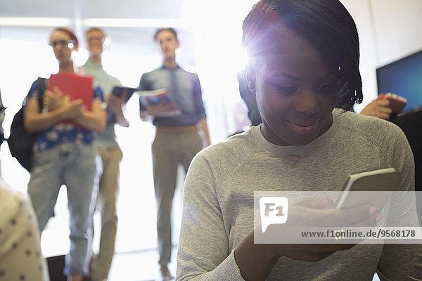 Porträt einer lächelnden Studentin  die mit anderen Studenten im Hintergrund auf das Smartphone schaut.