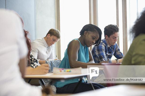 Blick auf die Schüler  die während des Tests im Klassenzimmer am Schreibtisch sitzen
