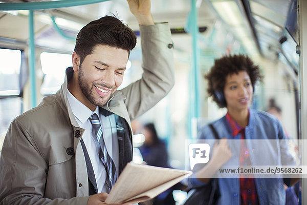 Geschäftsmann liest Zeitung im Zug