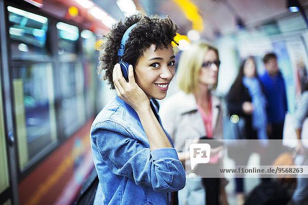 Lächelnde Frau hört Kopfhörer in der U-Bahn