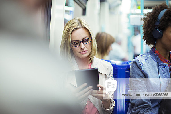 Geschäftsfrau mit digitalem Tablett im Zug