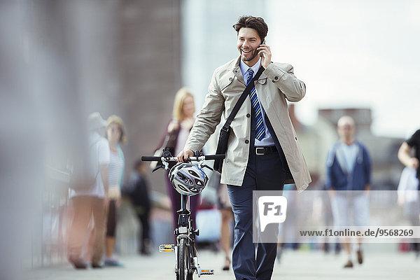 Geschäftsmann im Gespräch auf dem Handy schiebt Fahrrad in der Stadt