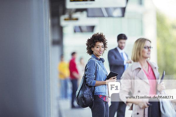 Frau hält digitales Tablett und wartet auf Zug im Bahnhof
