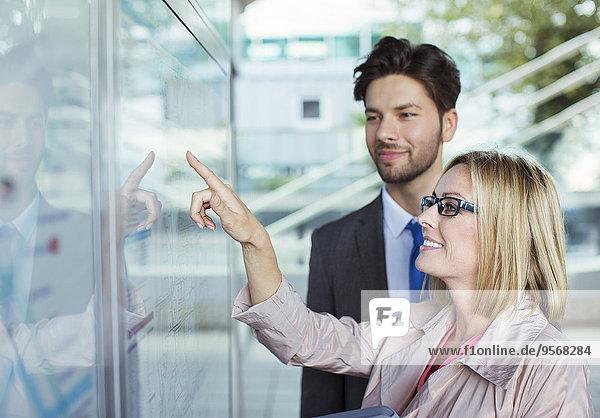 Geschäftsleute beim Lesen des Fahrplans
