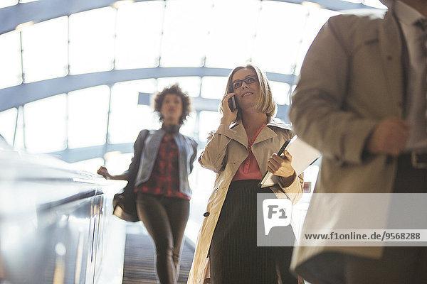 Niederwinkelansicht von Geschäftsleuten auf einer Rolltreppe