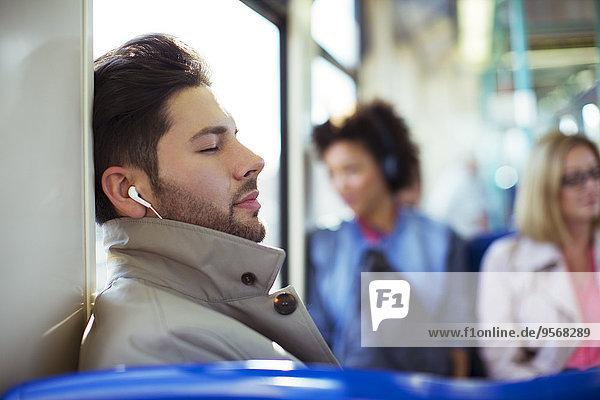Geschäftsmann schläft und hört Ohrstöpsel im Zug