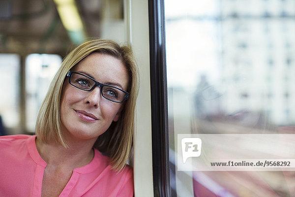 Lächelnde Frau schaut aus dem Zugfenster