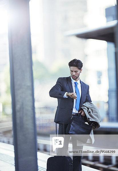 Geschäftsmann beim Prüfen seiner Uhr im Bahnhof