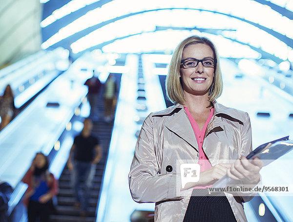 Geschäftsfrau mit Mappen in der Nähe der Rolltreppe