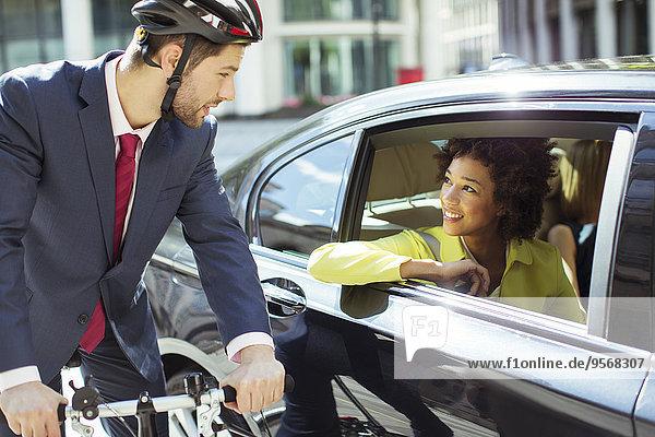 Geschäftsmann auf dem Fahrrad im Gespräch mit Frau im Auto