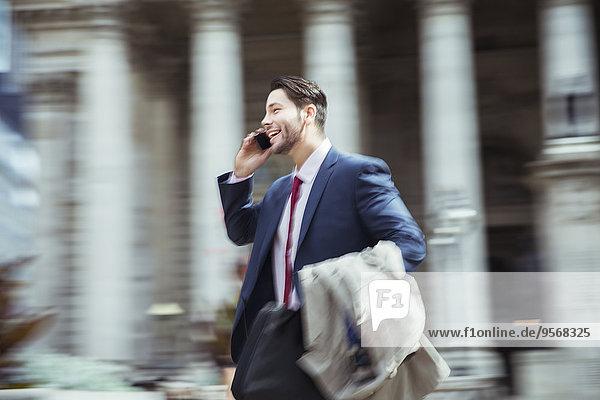 Verschwommener Blick auf den Geschäftsmann, der in der Stadt auf dem Handy spricht