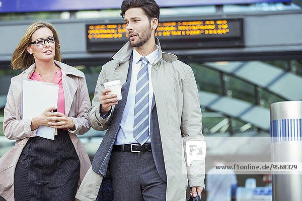 Geschäftsleute beim Gehen und Reden im Bahnhof