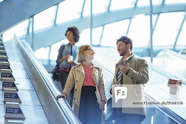 Geschäftsleute im Gespräch auf der Rolltreppe
